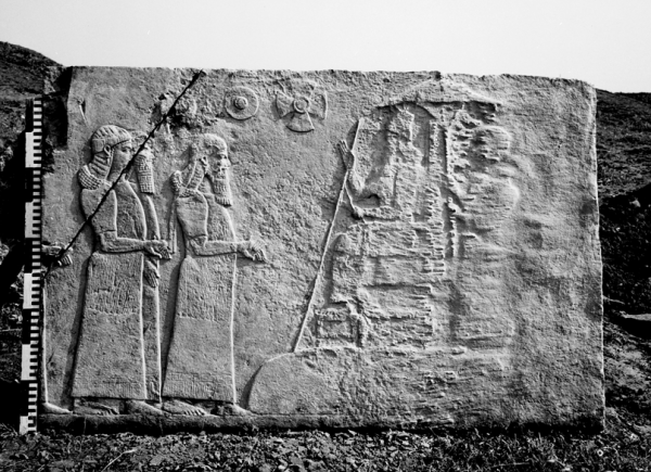 Relief fragment showing dignitaries before the king of Assyria sitting on a throne.